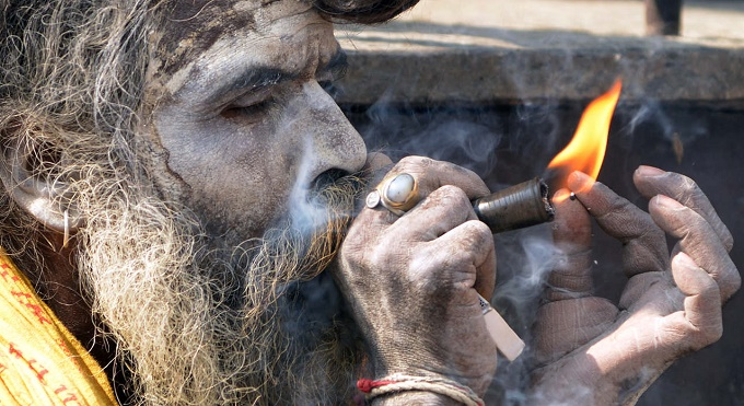 A Sadhu smokes marijuana from a clay pipe as a holy offering for Lord Shiva, the Hindu god of creation and destruction, at the Pashupatinath temple during Maha Shivaratri in Kathmandu on March 10, 2013. Hindus mark the Maha Shivratri festival by offering special prayers and fasting. Hundreds of sadhu arrived in Pashupatinath to take part in the Maha Shivaratri festival. AFP PHOTO / Prakash MATHEMA
